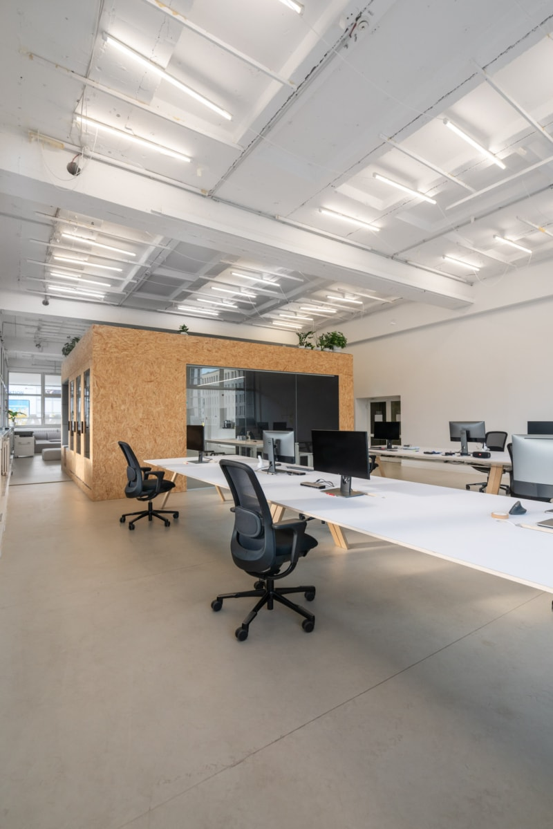 Arbeitstische und ein Meetingraum mit offenen und geschlossenen Telefonkabinen, Funktion und Design von muesiemue und maerzostudio für xcnt